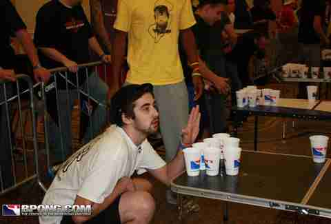 guy distracting another player in beer pong