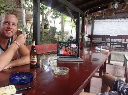 Dude at table enjoying beer and smoke