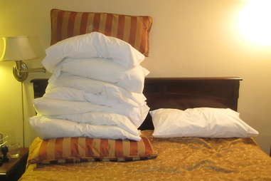 mountain of pillows on bed