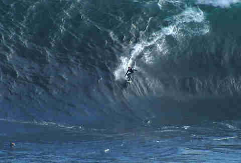 Guy surfing monster wave at ship stern bluff