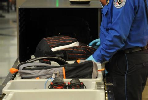 TSA security agent at airport checking baggage