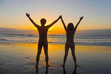 Couple nude on beach at sunset