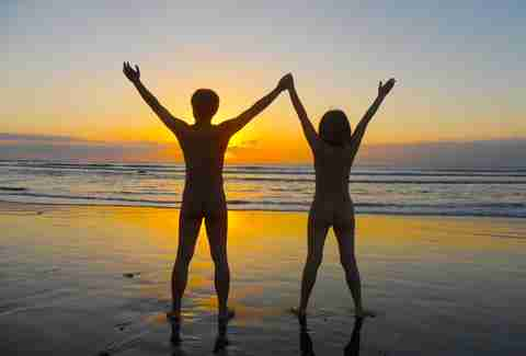Couple nude on beach at sunset