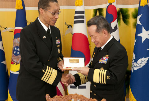 admiral shaking hands and giving gift