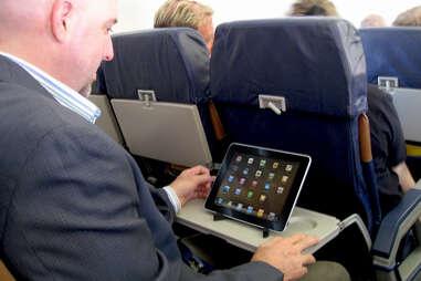 man using ipad on plane