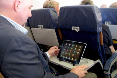man using ipad on plane