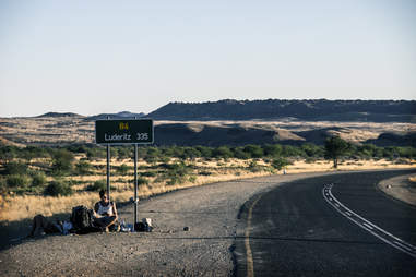 hitchhiking by a sign