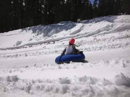 girl riding down hill in inner tube