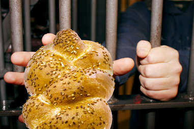 Prisoner locked up reaching for challah bread