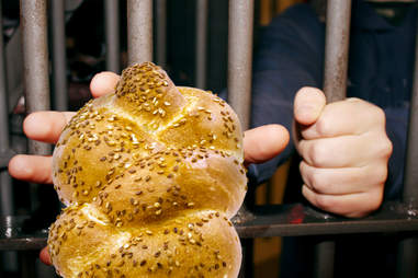 Prisoner locked up reaching for challah bread