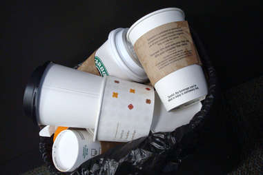 Trash can full of coffee cups