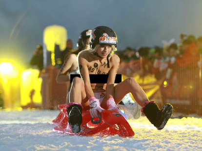Topless woman sledding