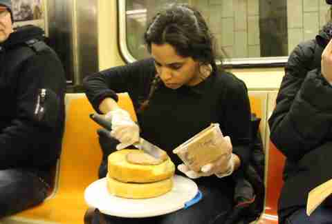 Woman frosting cake on the subway