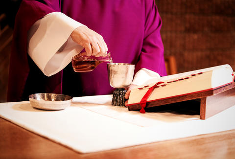 Priest pouring communion wine