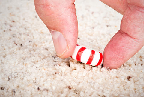 PIcking a peppermint candy off the carpet