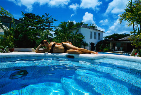 Woman lying by swimming pool