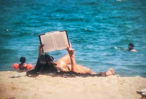 topless woman reading on beach