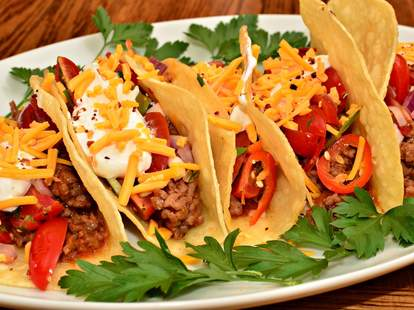 Beef, cheese, and tomato tacos lined up on a plate