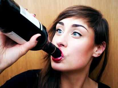 Woman drinking bottle of wine