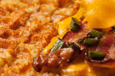 Tater tot waffle topped with bacon and roasted jalapenos to make a grilled cheese — Thrillist Recipes