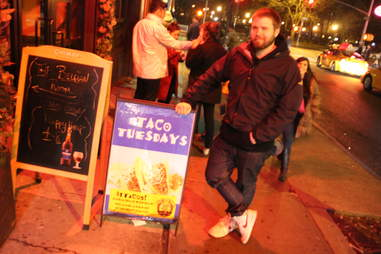 Cheapskate Tuesdays - Ben Robinson leaning on Hop Devil taco sign