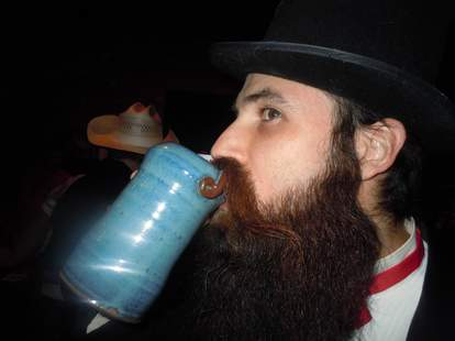 Mustached man drinking