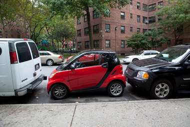 smart car parked in between two others in new york city
