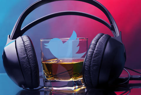 Twitter logo in glass of whiskey with headphones