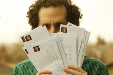 guy holding envelopes