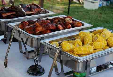 Metal catering containers filled with corn and BBQ