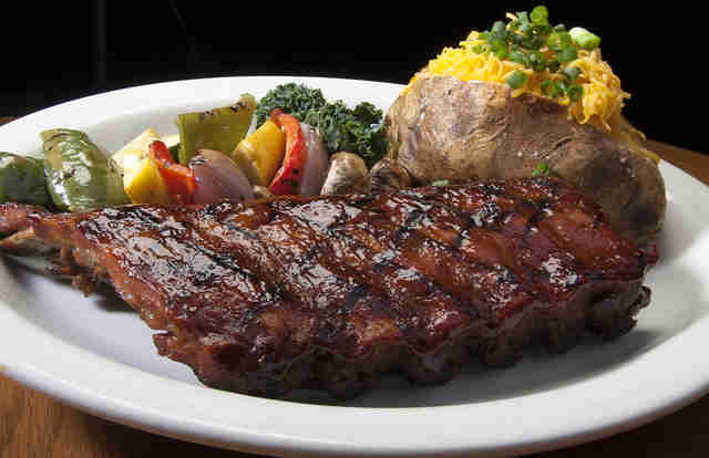 Large piece of steak with grilled veggies on a plate