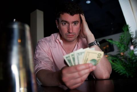 Man looking at handful of money