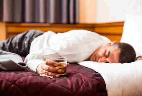 man asleep with whiskey in bed