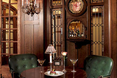 green leather chairs and wooden table with martinis at The Oak Bar