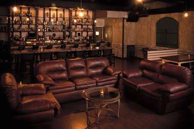 leather chairs, sitting area at Amari Bar