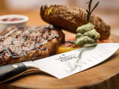 meat on a cutting board and knife harbour club