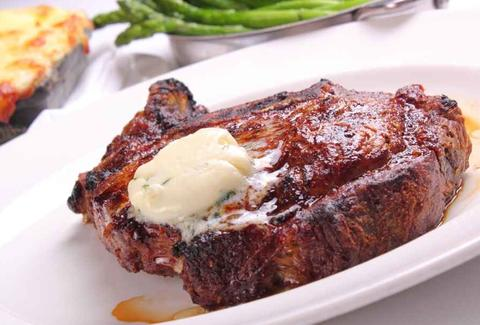 close up of steak with butter and asparagus at delmonico's steakhouse la vegas