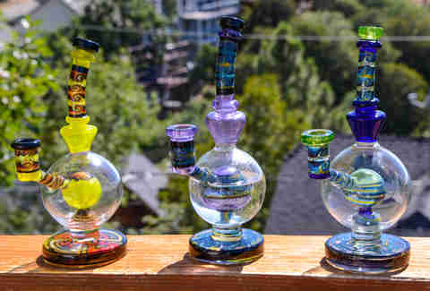 colorful dab rigs sitting on wooden balcony outside
