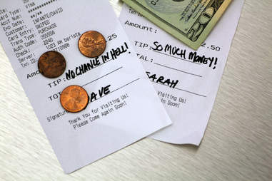 Things You Should Never Do at a Restaurant close up of bills money and change at a restaurant