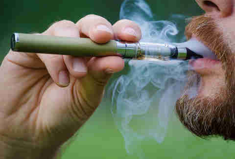 bearded man blowing smoke from a vape pen