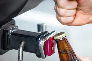 Man using BROpener one-piece bottle opener gadget