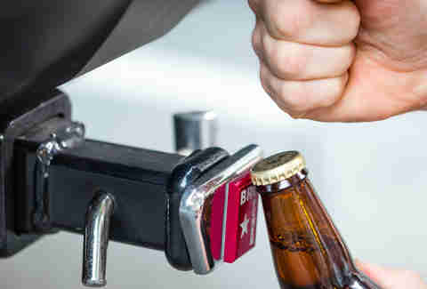 Man using BROpener one-piece bottle opener gadget