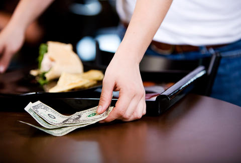 Man leaving tip on table