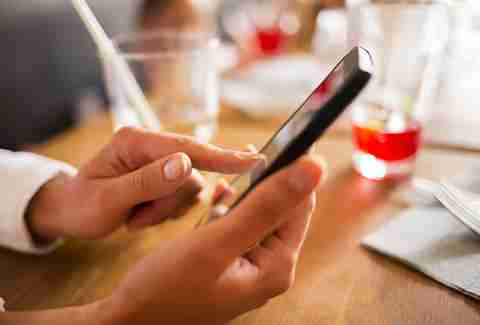 Woman on iPhone at dinner table with drinks