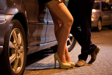 man and woman prostitute flirt in the street against a car