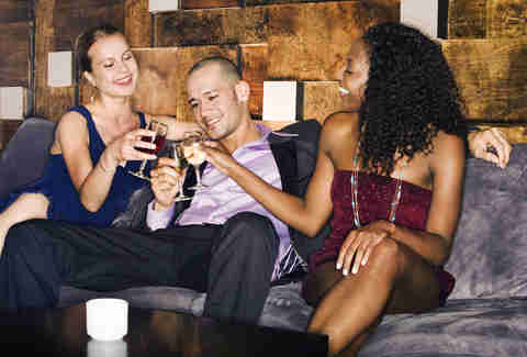 man and two woman at a bar/lounge having drinks