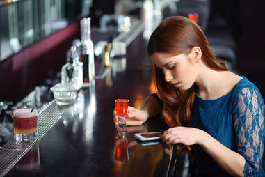 woman waiting at bar with a drink, on her phone