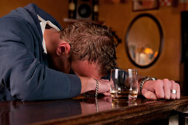 Man passed out at a bar surrounded by drinks