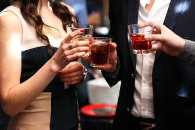 two men and a woman enjoy whiskey and cocktails at a bar