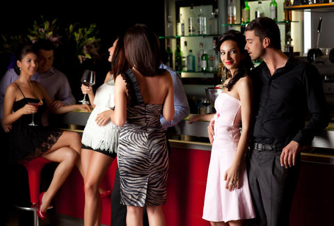 attractive people standing at a bar